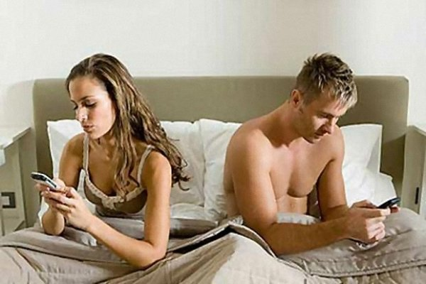 Couple in bed immersed in their phones