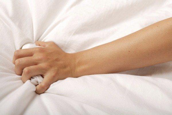 hand clutching bedsheets